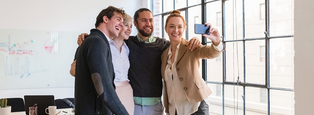 Four employees gathered together taking a selfie.